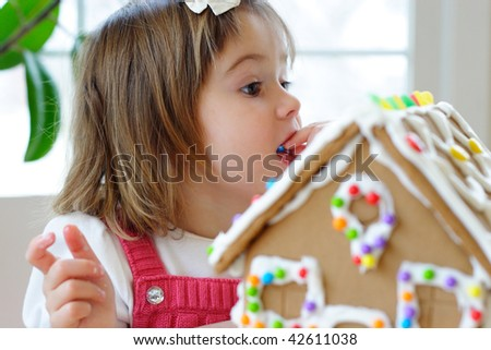 Little girl decorating gingerbread house and treating herself to candy - stock photo