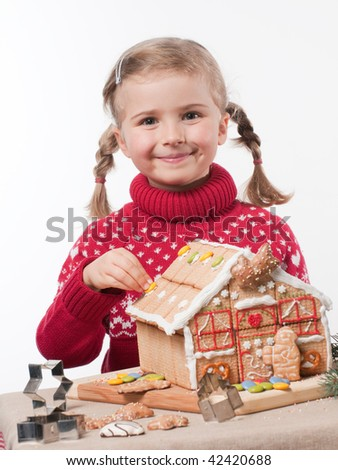 Little girl decorating oneself made christmas cookies house - stock photo