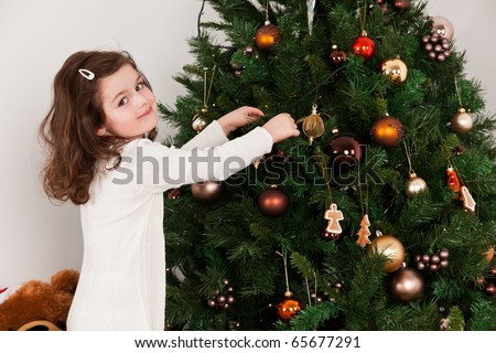 Little girl decorating the Christmas tree - stock photo