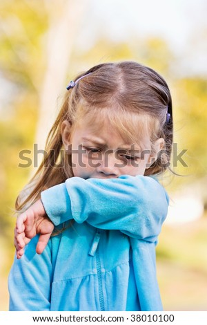 Little girl demonstrates coughing or sneezing into her sleeve to avoid spreading unwanted germs. - stock photo