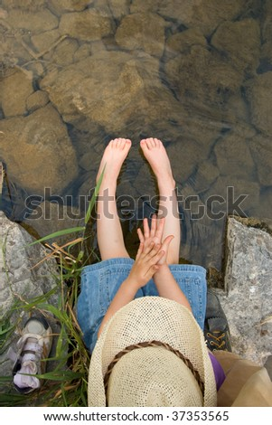 Little girl dipping her feet in a mountain creek. - stock photo