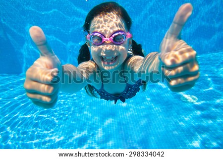 little girl dives into the water and shows the gesture OK - stock photo