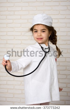 Little girl doctor in the white uniform with a stethoscope - stock photo