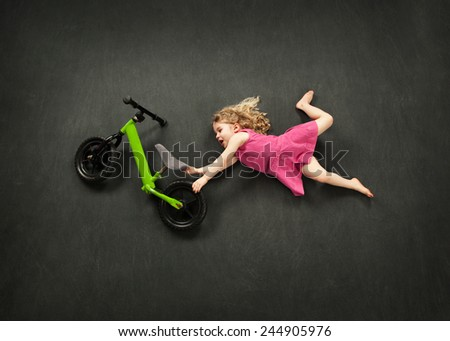 Little girl doing a bike jump stunt - stock photo