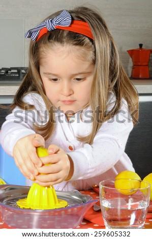 Little girl doing a lemon juice. - stock photo