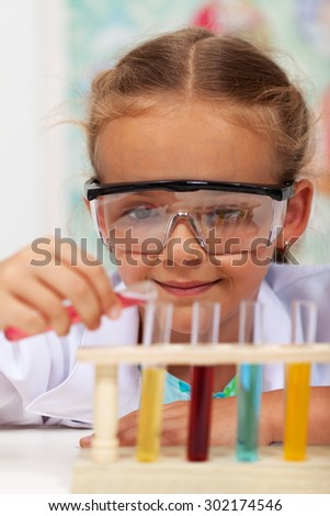 Little girl doing basic chemistry experiments - mixing different chemical solutions - stock photo