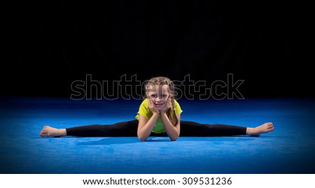 Little girl doing gymnastic exercises on black - stock photo