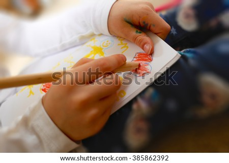 Little girl drawing a picture of her family for her Mum on Mother's Day. Including a red heart expressing the child's love, child's hands, sketch book & pencil/pen - stock photo