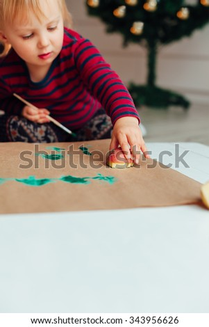 Little girl drawing Christmas tree with the stamp of potatoes, copy space