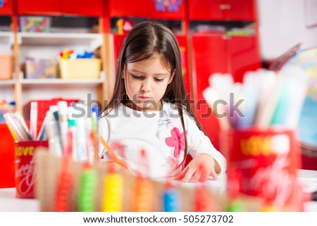 Little girl drawing on her book and having fun at play table