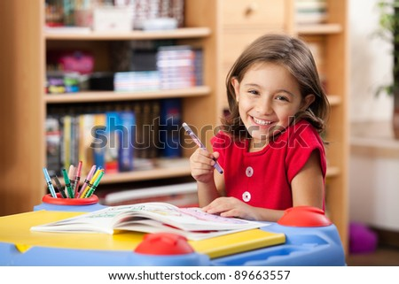 little girl drawing on her book and having fun at playtable - stock photo