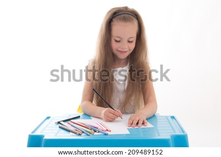 Little girl drawing using color pencils isolated on white background