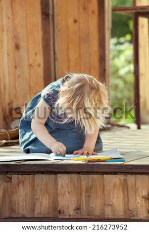 Little girl drawing with colored pencils on a country house wooden porch, outdoor natural light setting - stock photo