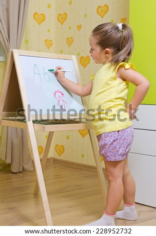 Little girl draws a marker on white board - stock photo