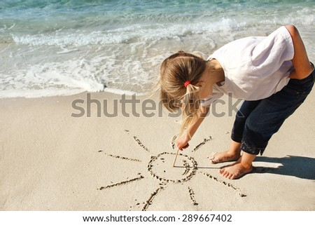 little girl draws a sun in the sand on the beach - stock photo
