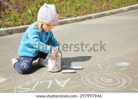 little girl draws chalk on asphalt. child playing in the open air in the summer - stock photo