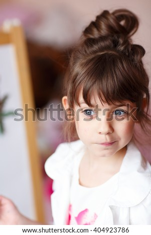 little girl draws on the easel - stock photo