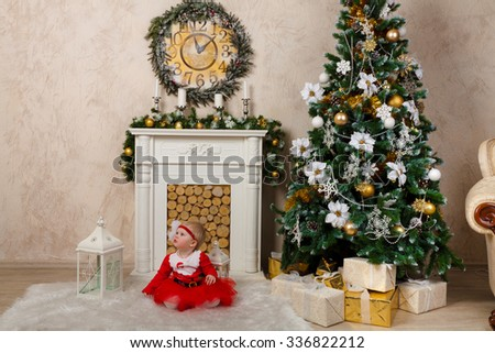 Little girl dressed as an elf is sitting under Christmas tree.