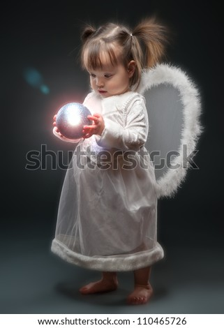 Little girl dressed as angel holding Christmas ornament - stock photo