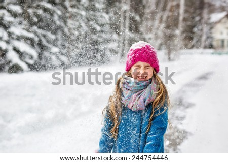 Little girl dressed in a blue coat and a pink cap closed her eyes with joy - stock photo
