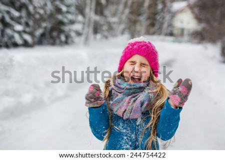 Little girl dressed in a blue coat and a pink hat joking screaming in the winter forest - stock photo
