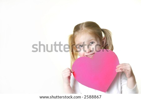 Little girl dressed in white holding a valentine heart