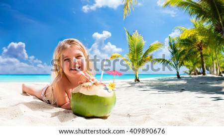 Little Girl Drinking Coconut Cocktail On Tropical Beach - Beach Holidays  - stock photo
