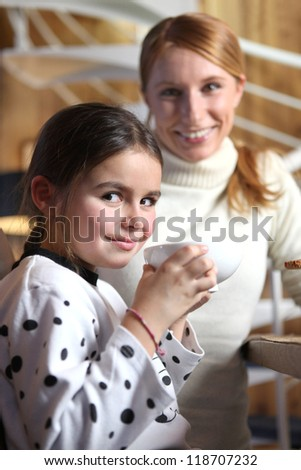 Little girl drinking from large mug at breakfast - stock photo