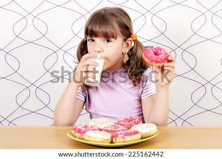 little girl drinking milk and eating donuts - stock photo