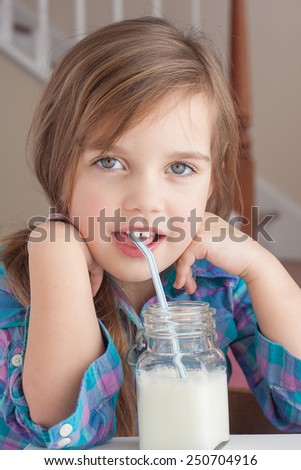 little girl drinking milk and looking at you - stock photo
