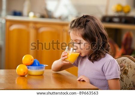 little girl drinking orange juice in the kitchen - stock photo