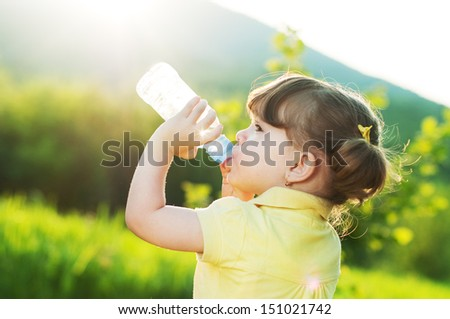 Little girl drinking water from a bottle against a sun background - stock photo