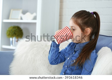 Little girl drinking water from cup in living room