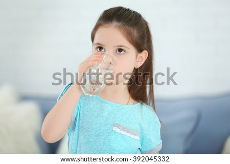 Little girl drinking water from glass in living room - stock photo