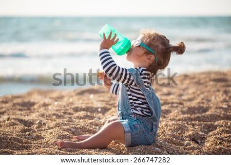 Little girl drinking water  on the beach - stock photo