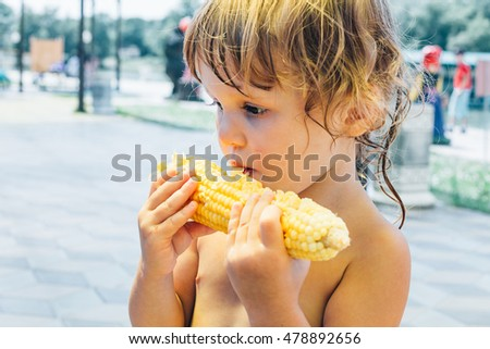 Little girl eat corn, close-up photos.