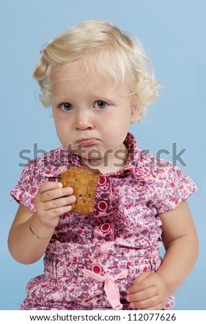 Little girl eating a biscuit. Isolated on blue background