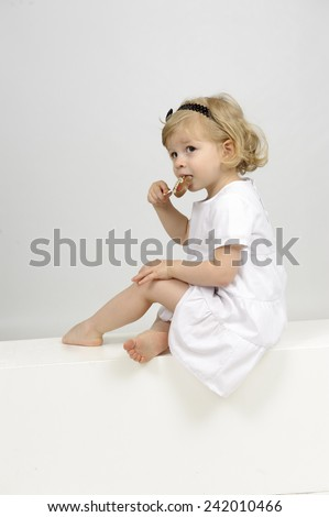 little girl eating a chocolate lollipop - stock photo