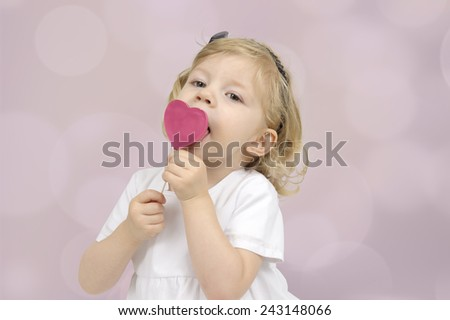 little girl eating a chocolate lollipop