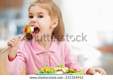 little girl eating a fresh salad - stock photo
