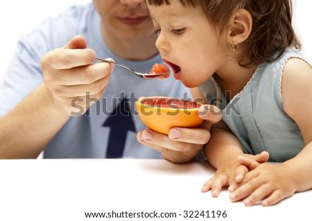 little girl eating a grapefruit - stock photo