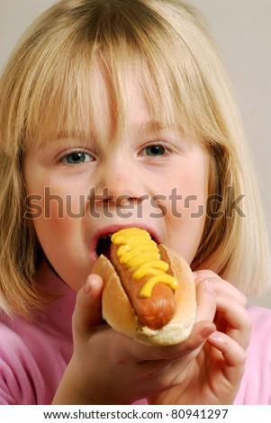 Little girl eating a hot dog.Kid eating hot dog. - stock photo