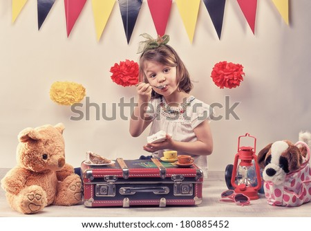 Little girl eating a piece of cake on the suitcase with her friend the teddy bear. Red lantern, pampoms, and fanions are the picnic background. - stock photo