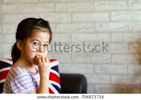 Little girl eating bread with copy space, selective focus.