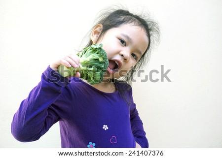 Little girl eating broccoli - healthy food - stock photo
