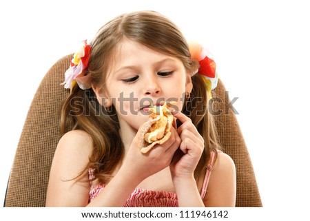 Little girl eating cake, isolated on white background - stock photo