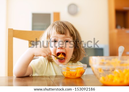 Little girl eating carrot salad  in home - stock photo