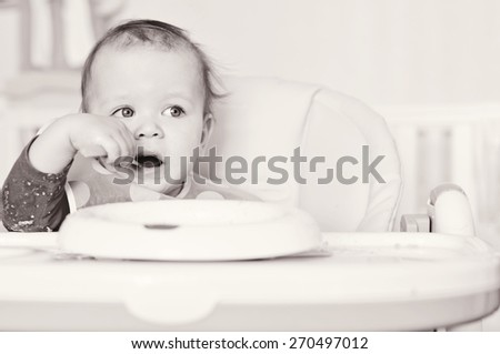 little girl eating cereal on her own - stock photo