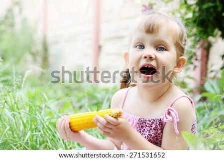 Little girl eating corn in the garden - stock photo