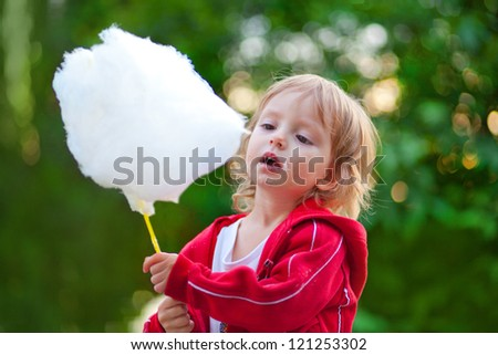 Little girl eating cotton candy in the park in spring - stock photo